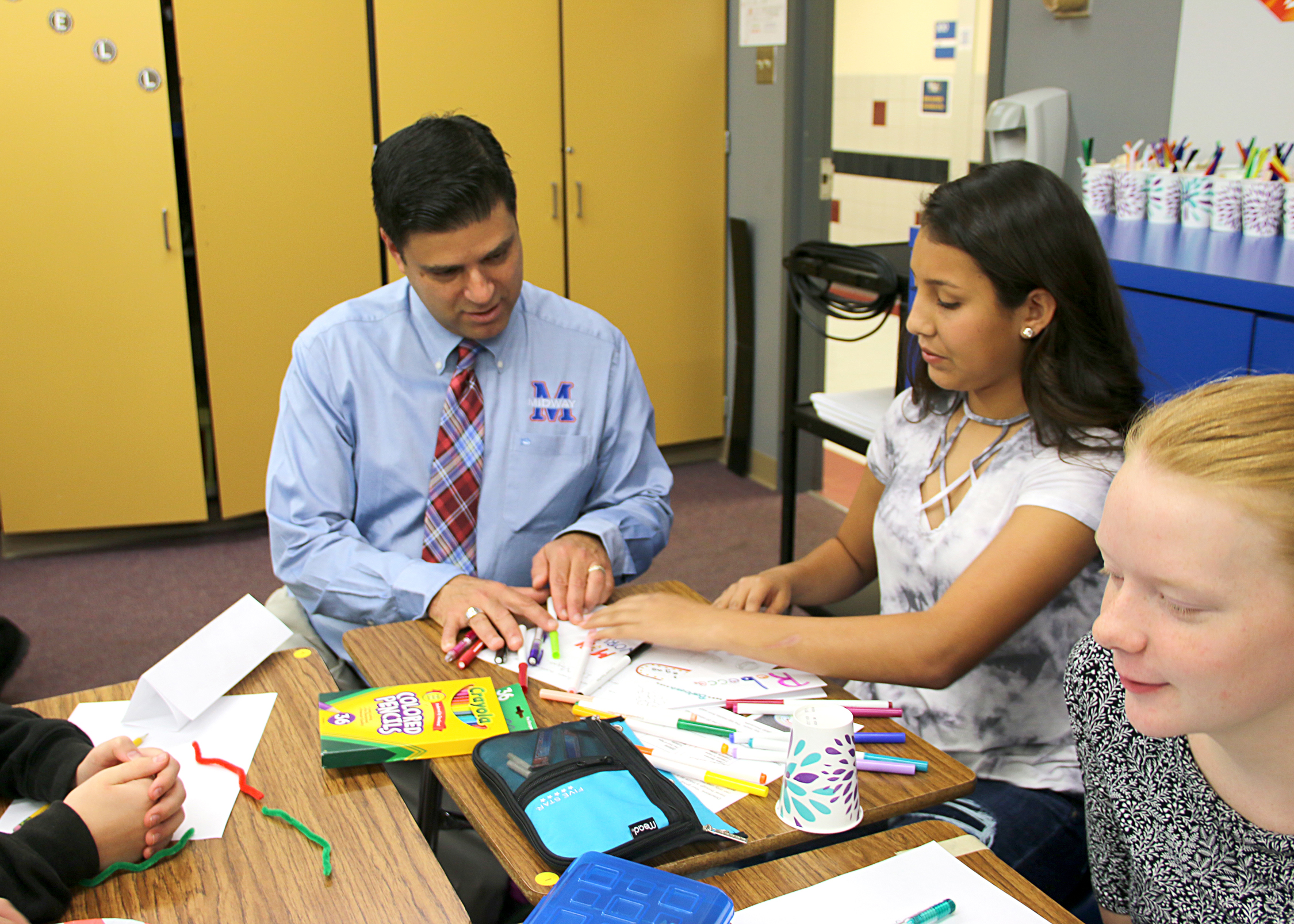 Dr. George Kazanas working with a middle school aged child at a desk
