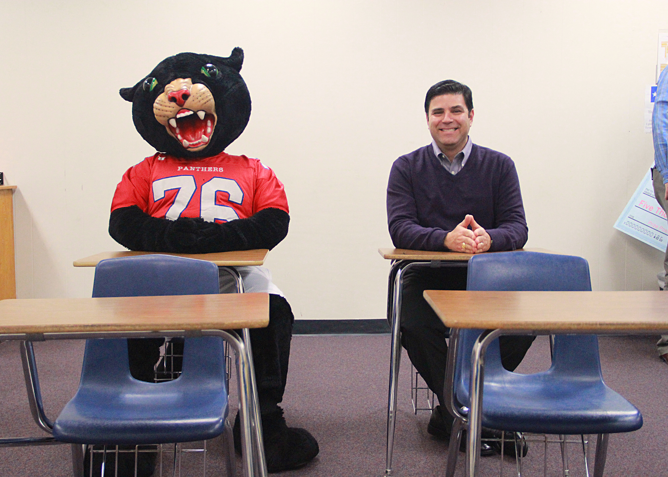 Dr. George Kazanas sitting in a desk next to the Midway Mascot at another desk to his right